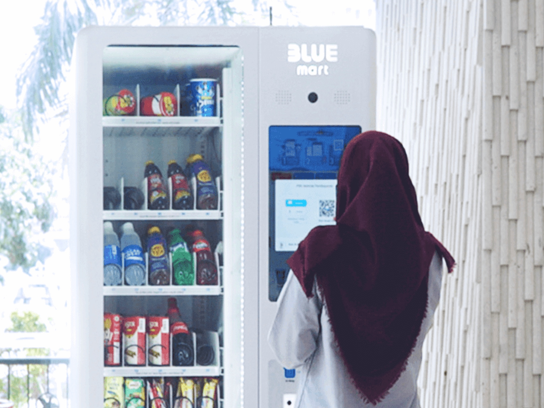 Indonesian Woman Scans the QR Code of BLUEmart vending machine to proceed with the payment. PHOTO: Credit to Blue Mobile