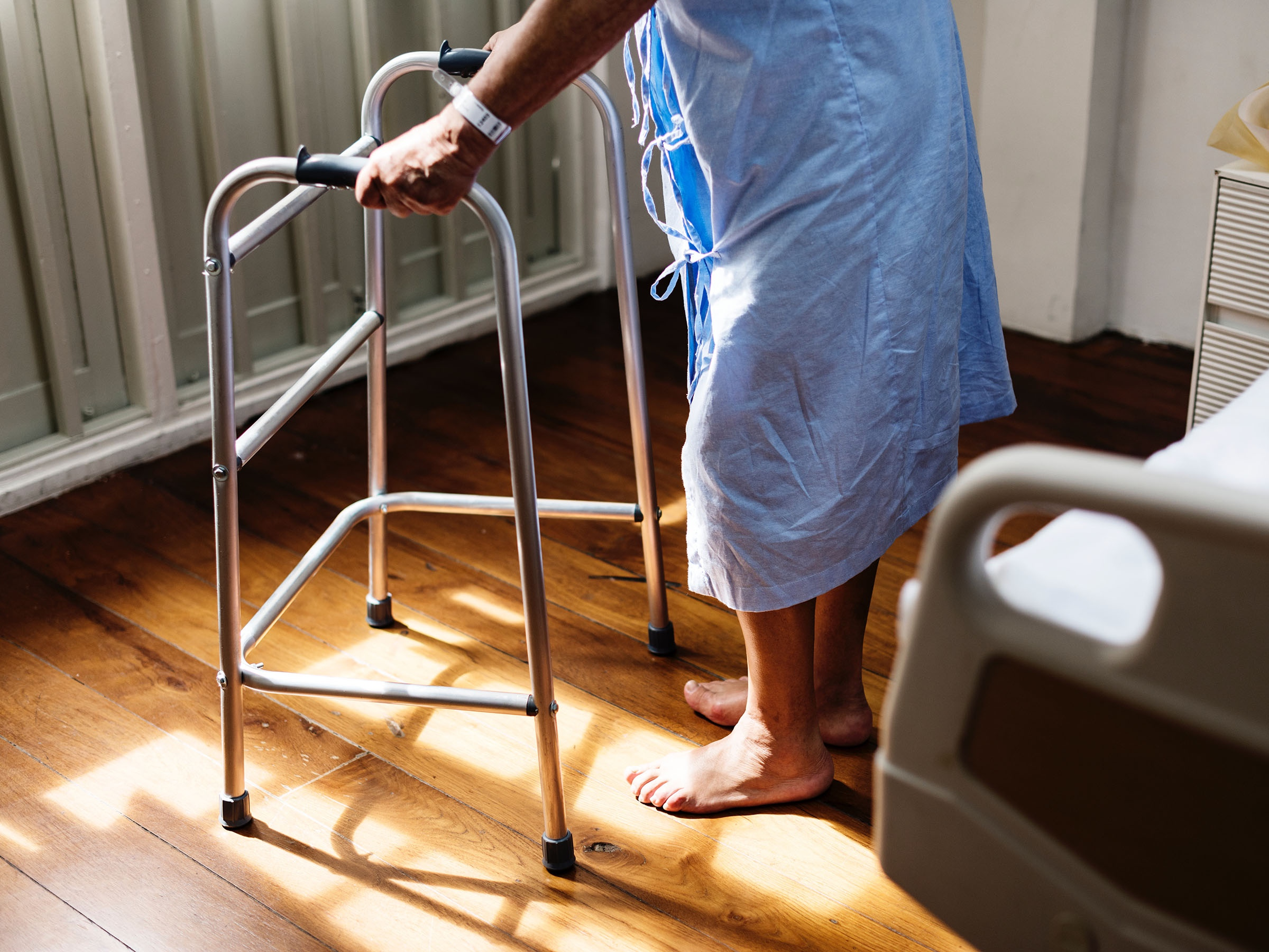 Person in hospital gown using walking frame beside hospital bed. Image Credit: rawpixel.com from Pexels